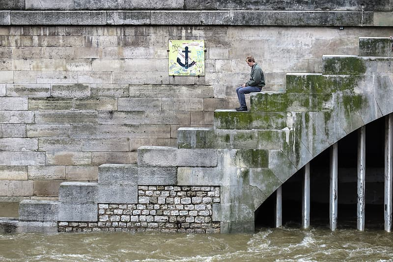A man sits on steps leading to the flooded Seine river in Paris, France