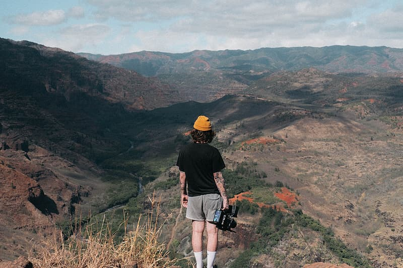 Woman standing on cliff holding video camera