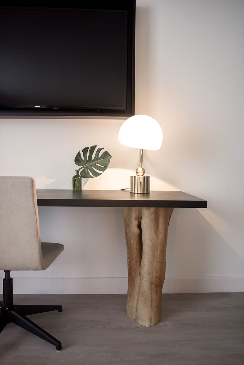 Stainless Steel Base White Shade Table Lamp on Brown Wooden Desk Near White Painted Wall With Wall Mounted Flat Screen T V