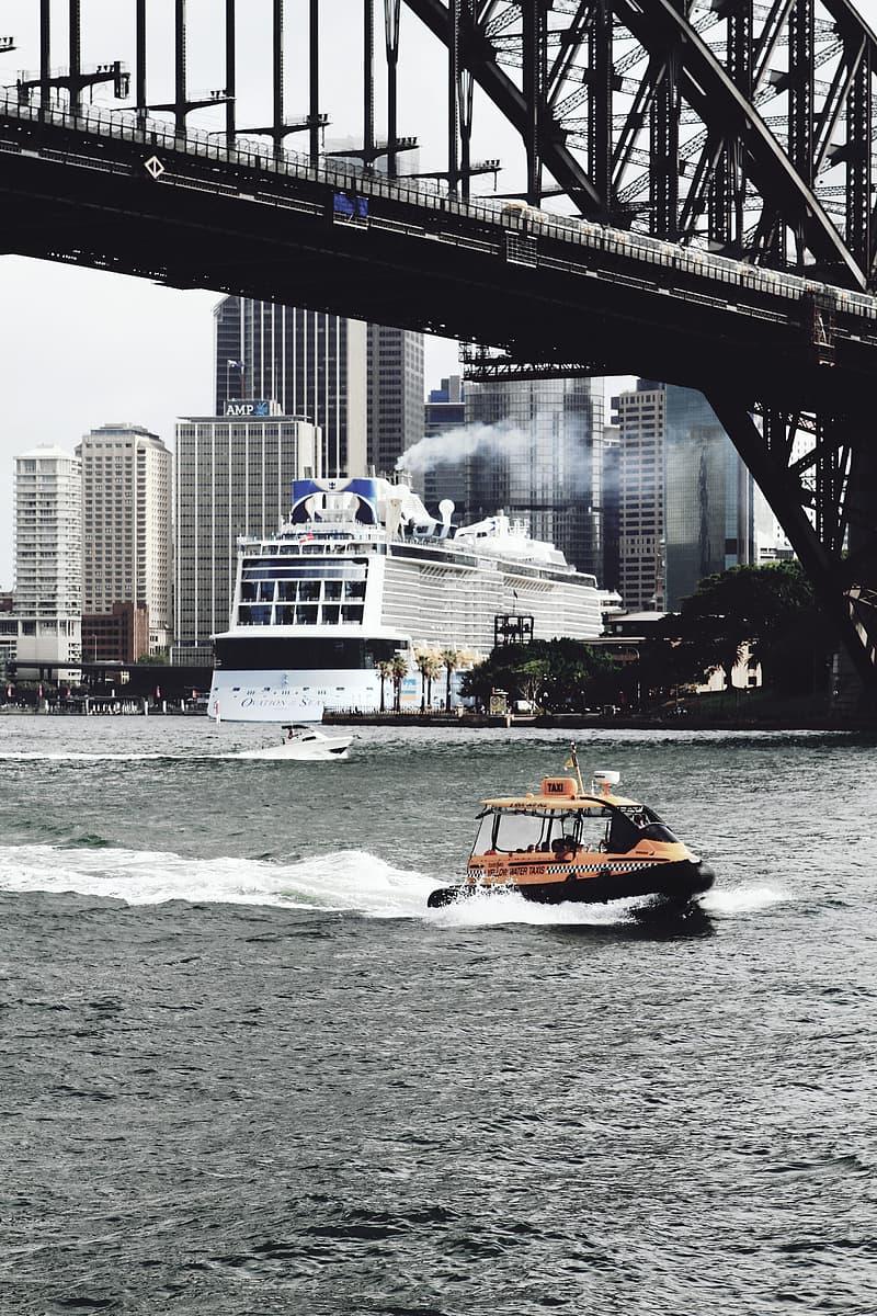Orange bow rider on under bridge on calm water