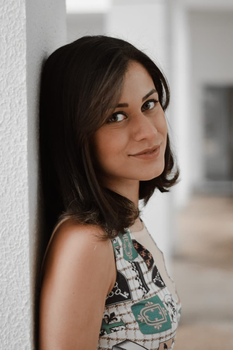 Woman Leaning on White Painted Wall and Smiling