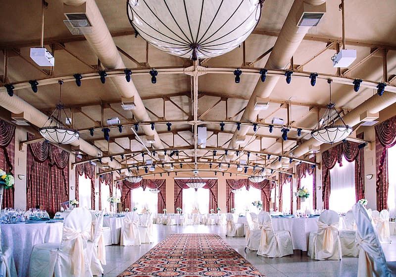 An elegant wedding hall with well arranged tables and chairs